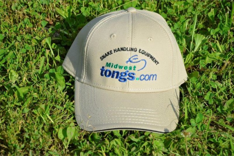 tan ball-cap with Midwest Tong's logo laying on grass