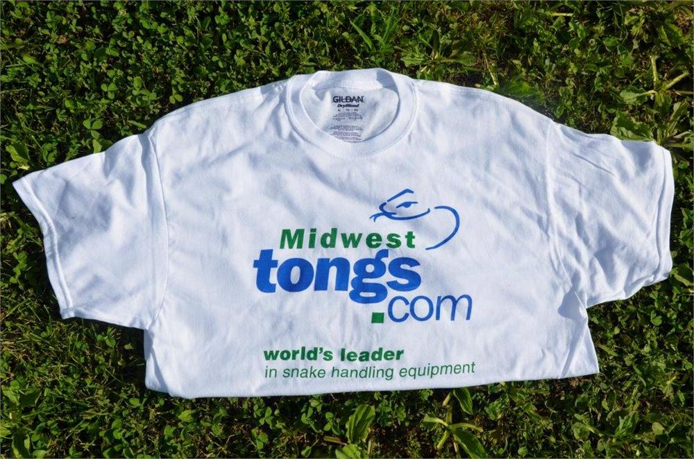 white folded t-shirt with Midwest Tong's logo laying on grass