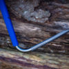 side view of professional titanium field hook in front of logs