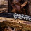 knife with tan and black snake skin handle on logs